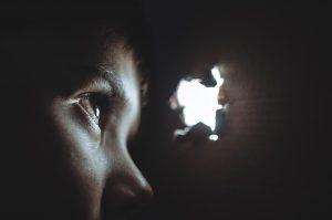 Personne qui regarde au travers d'un trou rempli de lumière, symbole d'espoir face à la violence conjugale