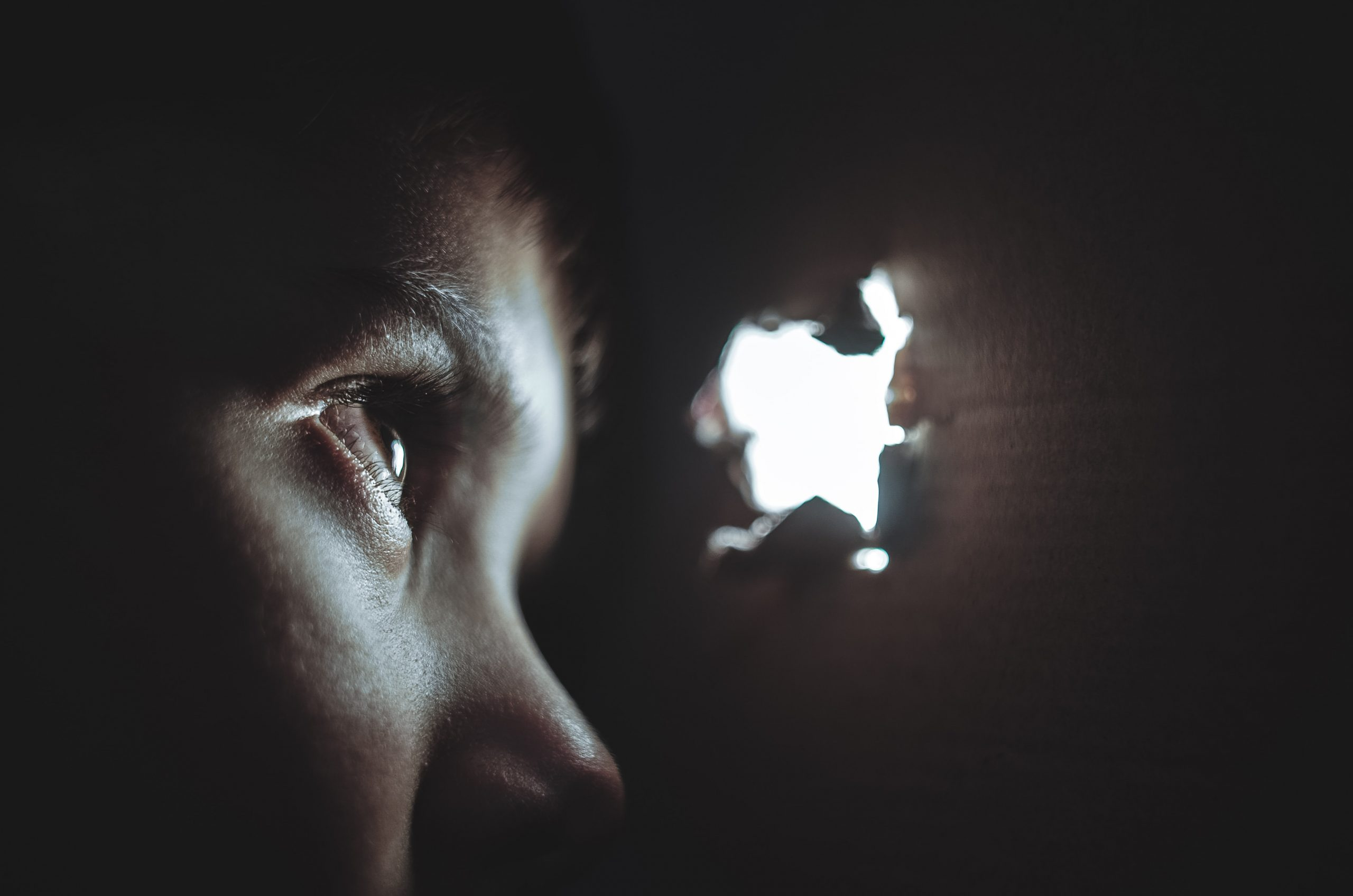 Domestic Violence victim looking through a light hole